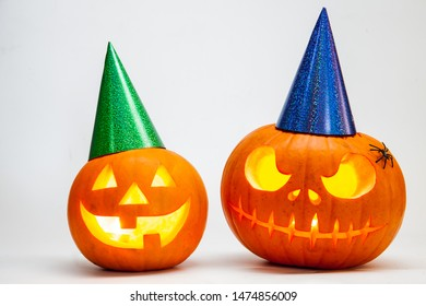 Two Halloween pumpkin head jack lantern with burning candles with festive hubcap isolated on white background