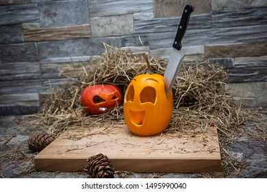 Two halloween pumpkins lie on a hay against the background of a stone wall. The knife is stuck in a yellow pumpkin Near the cones