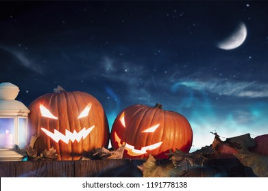 Two halloween pumpkins on fence with starry sky in the background. Horizontal orientation