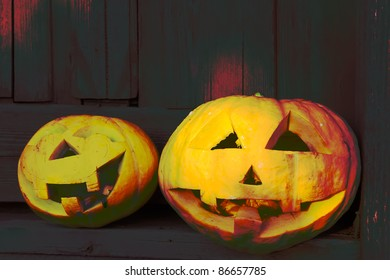 Two Halloween Pumpkins on wooden dark backdrop
