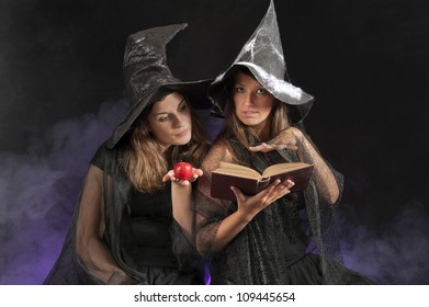 two halloween witches on dark smoky background