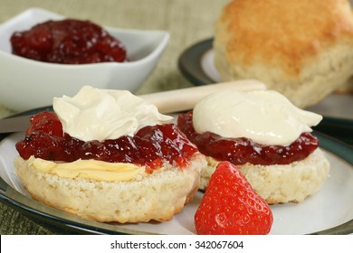 two halved devonshire scones with jam and fresh cream