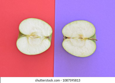 Two halves of an apple on two different colored backgrounds