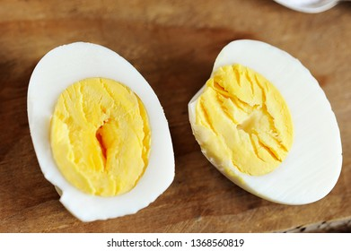 two halves of boiled egg on wooden rustic background