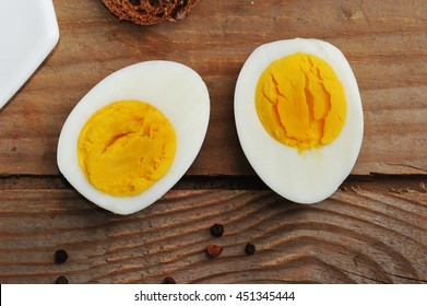 two halves of boiled eggs on wooden rustic background. the view from the top