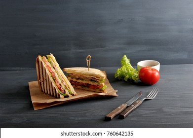 Two halves of the club sandwich on kraft paper. The filling of the sandwich consists of ham, cheese, tomato, bacon, sauce and fried egg. Nearby cutlery, mustard, vegetables. Dark background. Close-up.