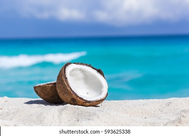 Two halves of cracked brown coconut on white sandy beach with turquoise sea background, close up