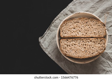 Two halves of a freshly baked organic wheat-spelt bread, sitting on linen.