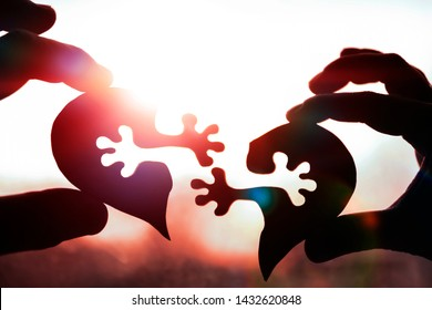 two halves of the heart, hands against the sky. love, relationships. longing for each other.