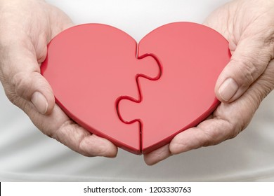Two Halves of One Heart. Erderly woman holding two pieces of jigsaw puzzle in form of a heart. Photography snapshot on the subject of 'Gender Relations'.