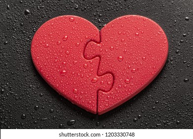 Two Halves of One Heart. Heart-shaped pieces of jigsaw puzzle lying on black colored background, all of which are covered with drops of water.
