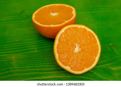 two halves of a ripe juicy orange on green ground