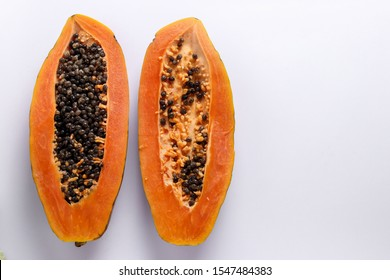 Two halves of ripe papaya on white background, horizontal orientation, copy space