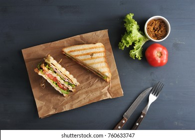 Two halves of a sandwich on kraft paper. The stuffing of the sandwich club consists of ham, cheese, tomato, bacon, sauce, fried egg. Nearby mustard and vegetables. Dark background. View from above.