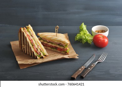 Two halves of a sandwich on kraft paper. The stuffing of the sandwich club consists of ham, cheese, tomato, bacon, sauce and fried egg. Nearby cutlery, mustard, vegetables. Dark background. Close-up.