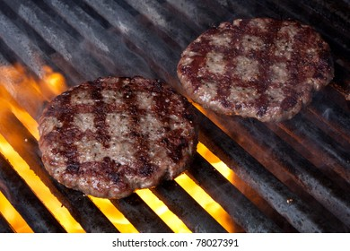 Two Hamburger Patties Cooking on Grill with Flames