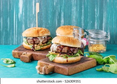 Two hamburgers with beef burger cutlet, fried onion, spinach, ketchup sauce and blue cheese in traditional buns, served on wood chopping board over bright turquoise background. Copy space