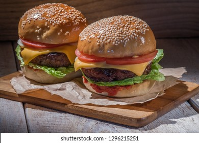 Two hamburgers on paper and wooden boards