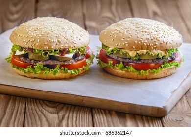 Two hamburgers on a sheet of paper on a wooden background.