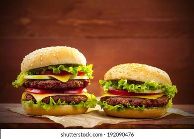 Two hamburgers on wood board