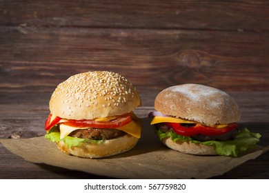 Two hamburgers on wood board over rustic background