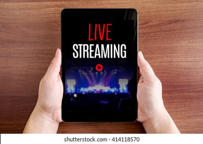 Two hand holding tablet with Live streaming and play icon on screen at dark brown table top,Digital business concept.