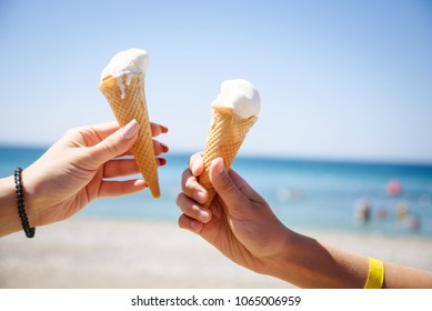 two hand with ice cream horns and sea on background