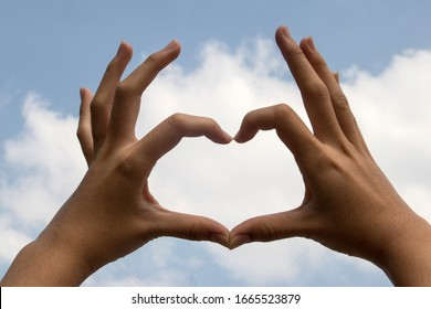 Two Hand in shape of love heart on Blue Sky and Cloudy.