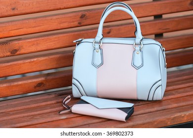 Two handbags on a bench in street. outdoor city