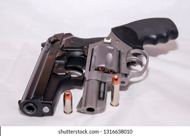Two handguns, a 357 magnum revolver and a black 40 caliber pistol each with a hollow point bullet next to it on a white background
