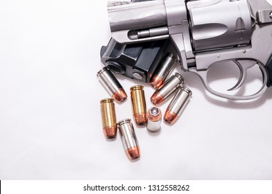 Two handguns, a 40 caliber pistol and a 357 magnum revolver with 40 caliber bullets on a white background