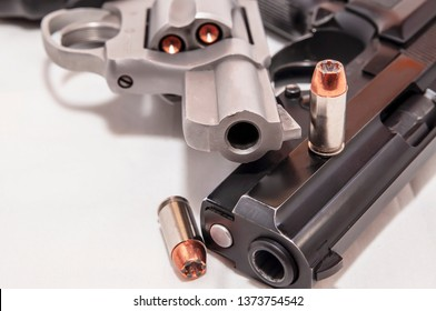 Two handguns, a 40 caliber pistol and a 357 magnum revolver on a white background with two 40 caliber bullets