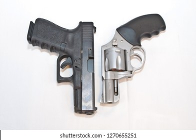 Two handguns, a black 9mm pistol and a silver 357 magnum revolver, loaded with gold hollow point bullets side by side on a white background