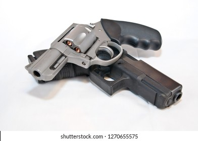 Two handguns, a silver 357 magnum revolver on top of a black 9mm pistol on a white background.  The revolver is shown loaded with gold hollow point bullets