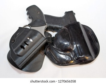 Two handguns, a silver 357 magnum revolver on top of a black 9mm pistol on a white background. Both shown in black holsters