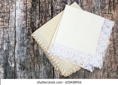 Two handkerchiefs with lace trim on an old wooden background.