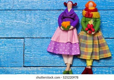 Two handmade doll girl tilda on blue wooden background. Holidays decoration. Interior fairy dolls