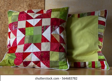 Two handmade quilted cushions with Christmas star pattern in Christmas colors green and red behind the cork wall are on the table