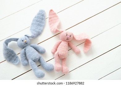 Two handmade rabbit toys male and female. Baby shower decoration ideas. DIY knitted toys for kids