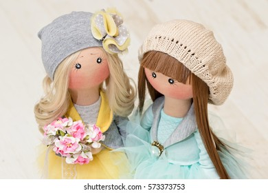 Two handmade rag dolls with natural hair - blonde and brown-haired, in knitted hats