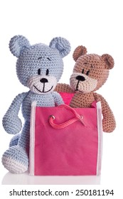 two handmade teddy bears with a pink bag