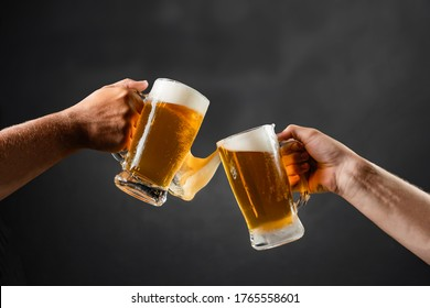 two hands with beer mugs, toasting in celebration, with overflowing foam, dark background and space for writing