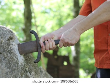 two hands of a boy takes a magical sword called Excalibur in the forest of Camelot