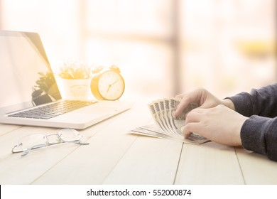 Two hands of a business man counting money or paying cash with computer laptop and clock.
