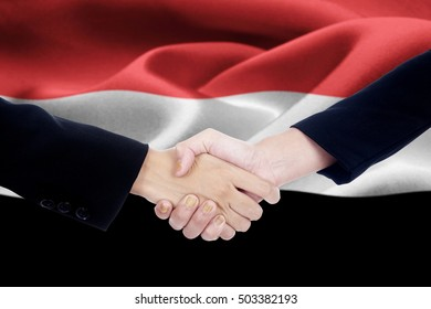 Two hands of business team are handshake in front of Yemen flag