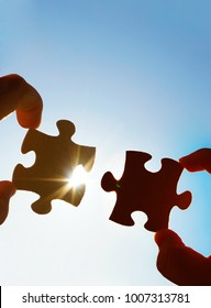two hands of businessman to connect couple puzzle piece with sky background.empty space.Jigsaw wooden puzzle against sun rays.two part of whole.symbol of association and connection.business strategy