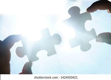 zwei Hände Geschäftsmann zu verbinden Puzzle-Stück mit Himmel Hintergrund.Jigsaw allein hölzernes Rätsel gegen Sonnenstrahlen.ein Teil des ganzen.Symbol der Verbindung und Verbindung.Geschäftsstrategie