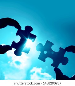 two hands of businessman to connect couple puzzle piece with sky background.Jigsaw alone wooden puzzle against sun rays.one part of whole.symbol of association and connection.business strategy