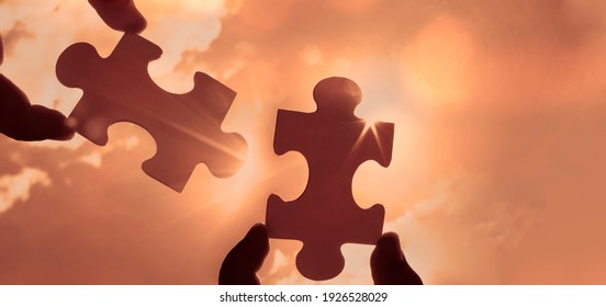 two hands of businessman to connect couple puzzle piece with sky background.Jigsaw alone wooden puzzle against sun rays.one part of whole.symbol of association and connection.business strategy.