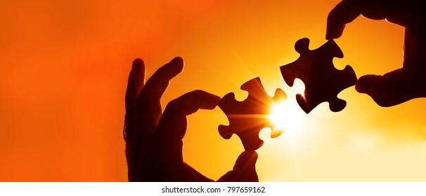 two hands of businessman to connect couple puzzle piece with sky background. wooden puzzle against sun rays.one part of whole.symbol of association and connection.business strategy